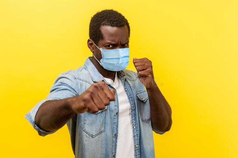 Ready for fight against coronavirus. Portrait of aggressive man with surgical medical mask standing in defensive posture, clenched. Fists, threatening to attack stock photo