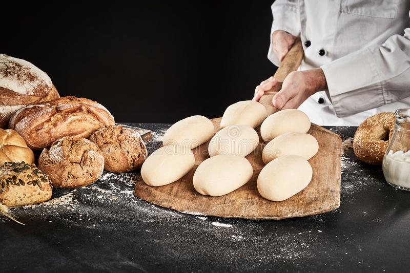 Ready formed loaves of bread on a wooden paddle stock images