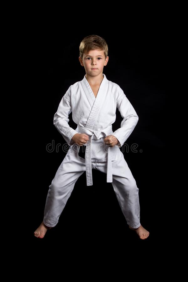 Ready front pose with lowered clenched fists. Kid in brand new white kimono on the black background royalty free stock photo