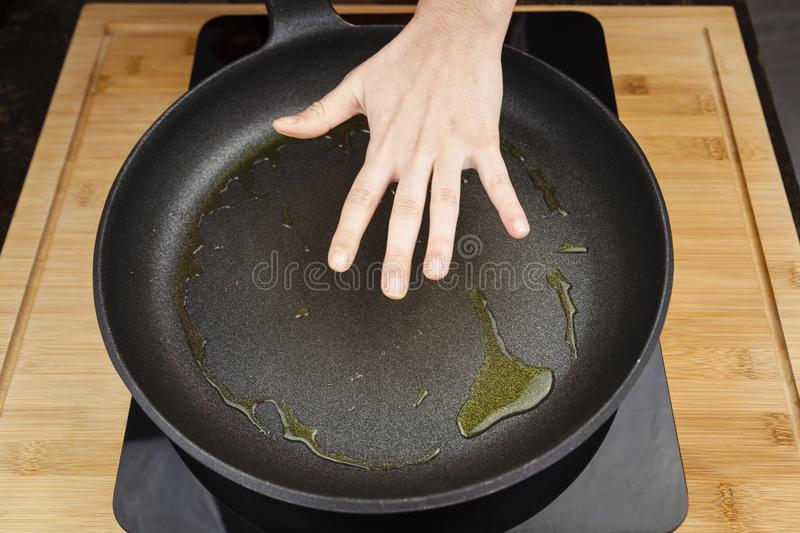 Ready for frying on the pan concept represented by hand cheking temperature. stock photos