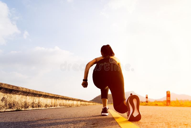Ready go. running woman on start position and going to run on long road stock photo