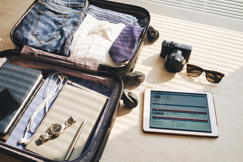 Ready for holiday. Close-up of packed suitcase for a new journey and touchpad with electronic ticket on the table stock photography