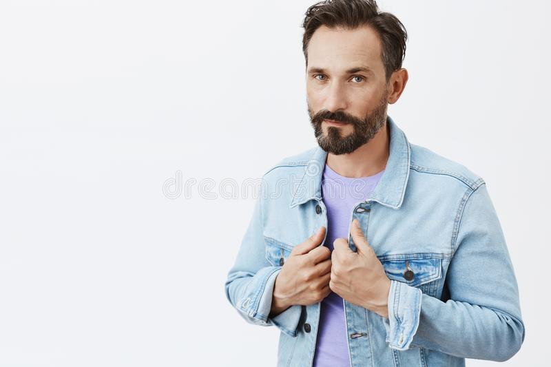 Ready impressed and conquer. Portrait of handsome and stylish confident male entrepreneur in denim jacket over purple t. Shirt, touching collar and staring with stock photography
