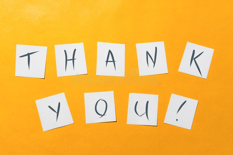Ready-made inscription `thank you` on white squares of paper on a gold background. royalty free stock images