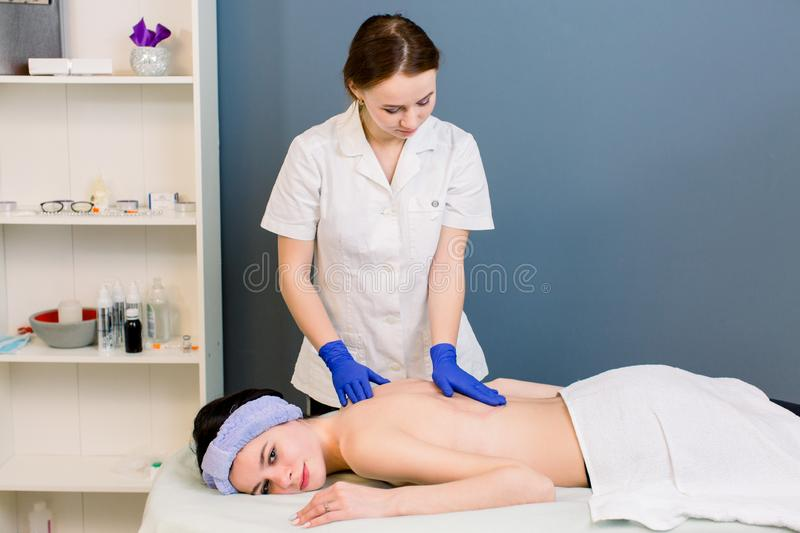Ready for massage - oil pouring on woman`s back in spa wellness center. Professional body massage to beautiful girl in stock images