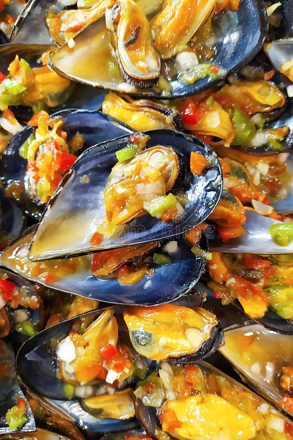 Ready mussel in the sink with vegetable salad. A plate of cooked mussels. Mussel shells lie on a plate royalty free stock image