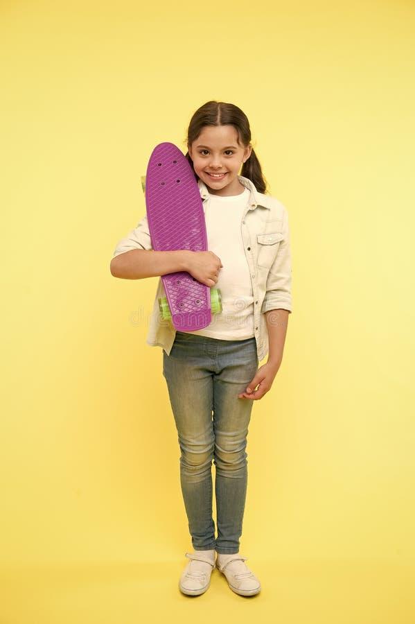 Ready per guidare La ragazza del bambino felice porta il bordo del penny Il bambino gradisce pattinare con il bordo del penny Hob fotografia stock
