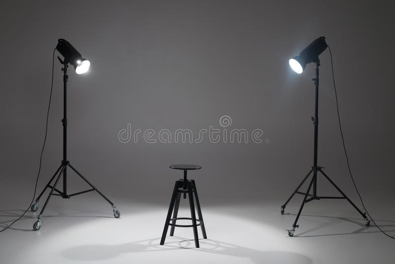 Ready photo shoot setup in white background in the studio. Photography Studio with Empty Chair. Lights in a photo studio on a white background are aimed at a stock photo