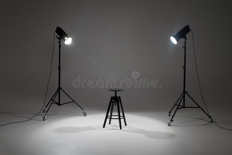 Ready photo shoot setup in white background in the studio. Photography Studio with Empty Chair. Lights in a photo studio on a white background are aimed at a royalty free stock photo