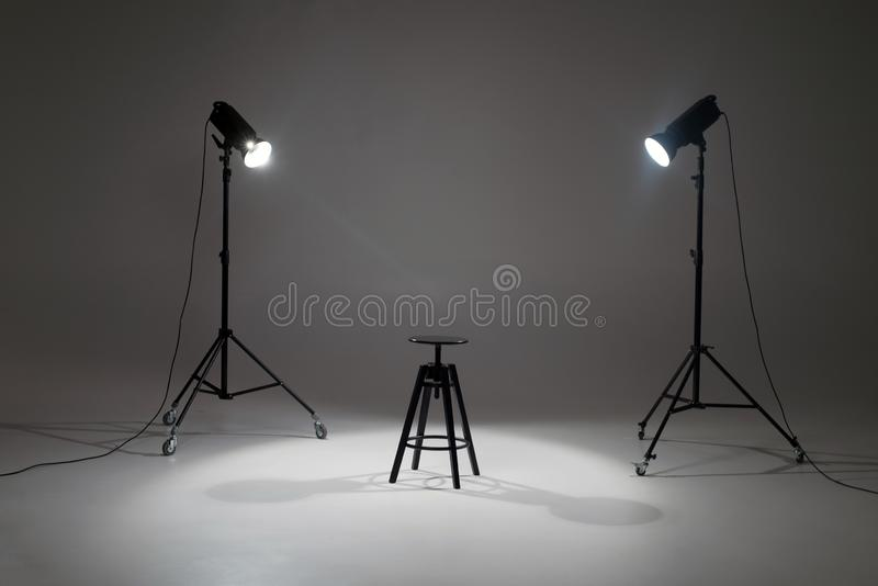Ready photo shoot setup in white background in the studio. Photography Studio with Empty Chair. Lights in a photo studio on a white background are aimed at a stock images