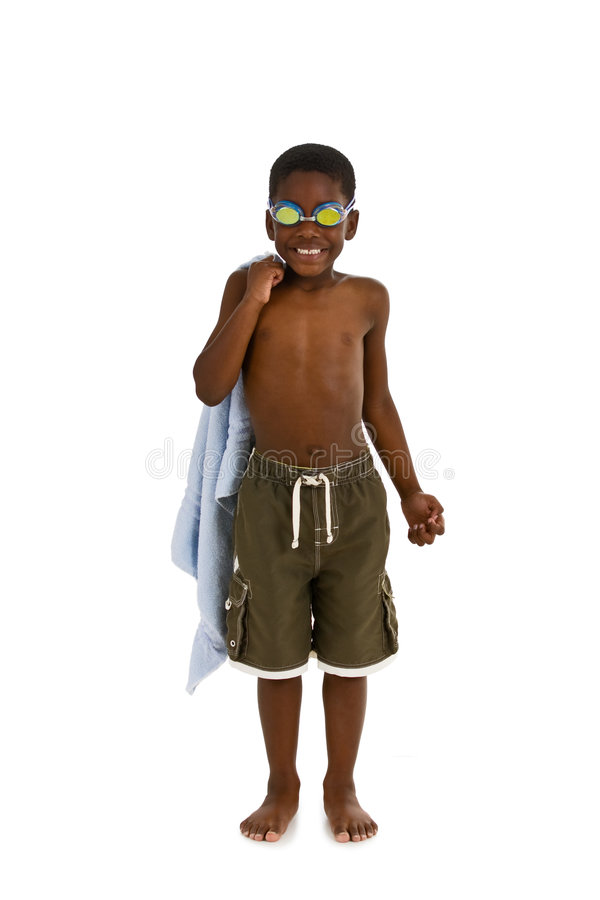 Ready for the Pool. A young African American boy wearing swim trunks and goggles, and carrying a towel. Isolated on a white background royalty free stock image
