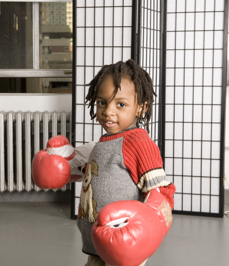 Ready for a punch. Little boy getting ready for a punch with boxing gloves stock photography