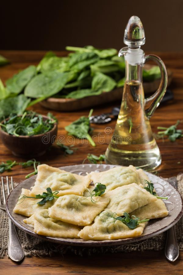 Ready ravioli in a plate, spinach, olive oil in a jar.  royalty free stock photo