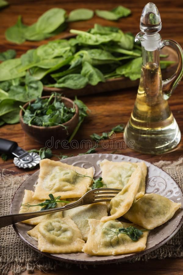 Ready ravioli in a plate, spinach, olive oil in a jar.  royalty free stock images