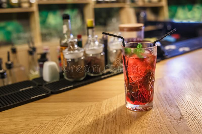 Ready red alcohol cocktail on background bars of spices in an elite bar for making cocktails Cinnamon Rosehip Clove Drunk Cherry.  royalty free stock image