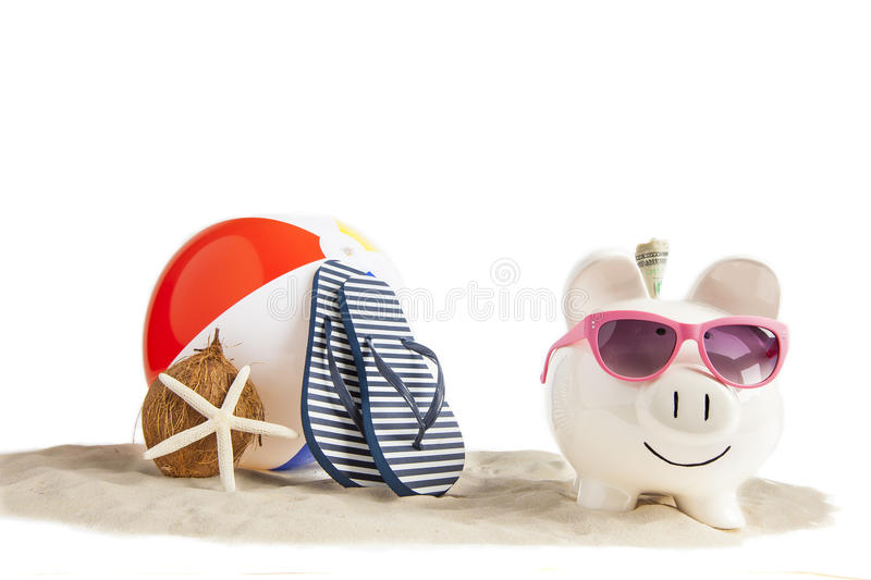 Ready, Set, Save for Fun Beach Vacation. Coconut Piggy bank in foreground with Colorful Beach Ball, Star Fish and Sandals, Flip Flops in Beach Sand in background royalty free stock photography