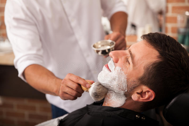Ready for a shave at the barber's. Barber putting some shaving cream on a client before shaving his beard in a barber shop stock photography