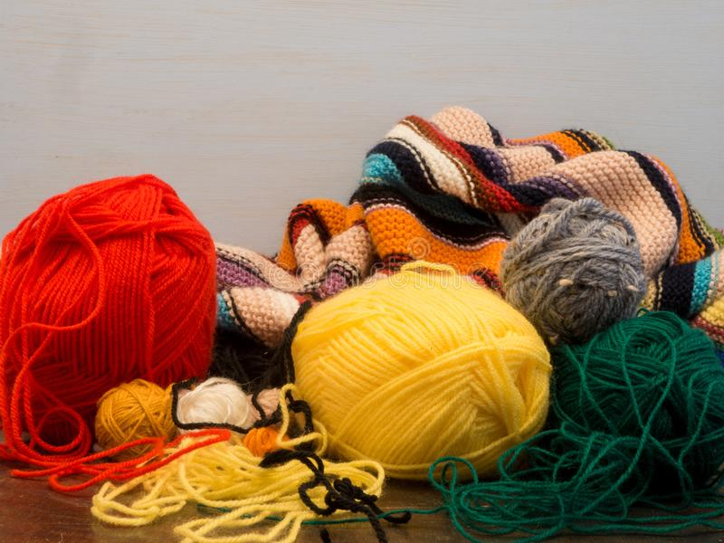 Wool image, with colorful knitted blanket and skeins of red, yellow and green wool royalty free stock image