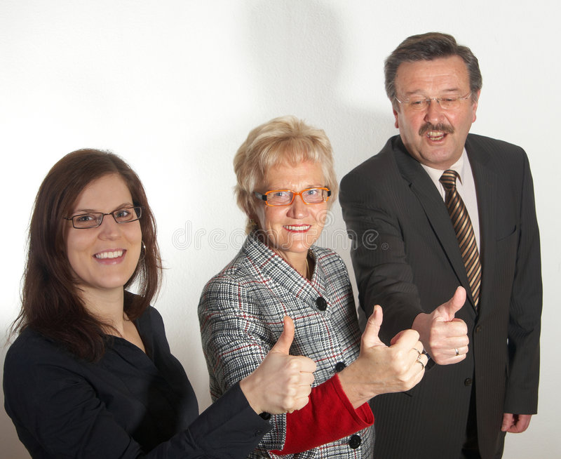 Ready steady. Small group of business people in business suits showing thumbs up. Focus is on the young woman in front royalty free stock photo
