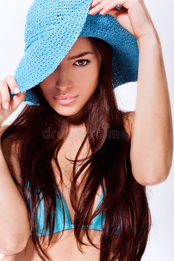 Ready for summer. Beautiful brunette wearing blue summer hat and bikini royalty free stock images