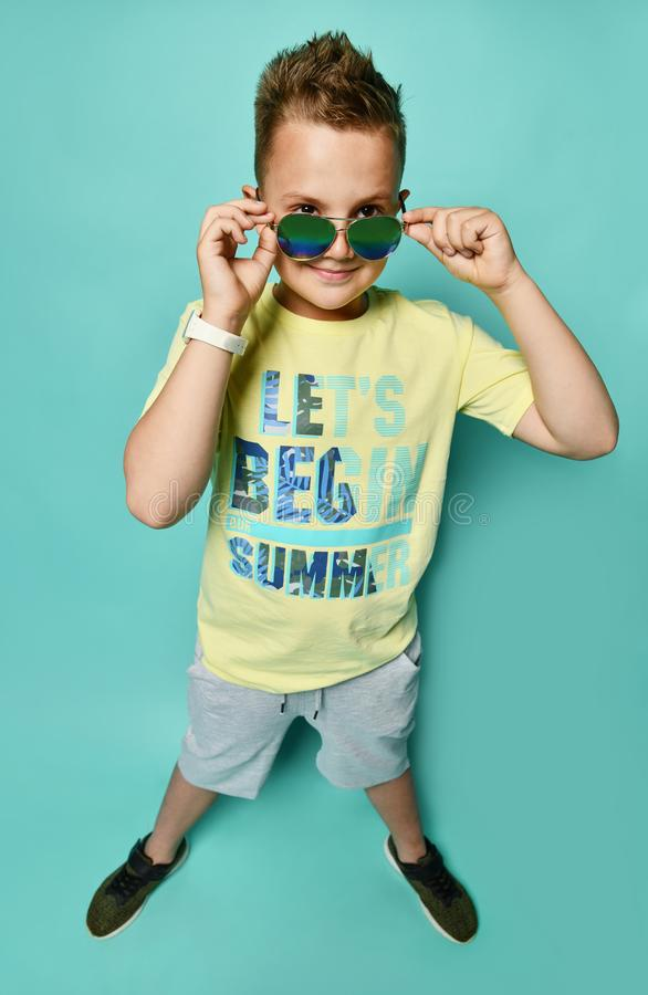Ready for summer vacation. Full length of cheerful young man adjusting eyewear and looking at camera royalty free stock photography