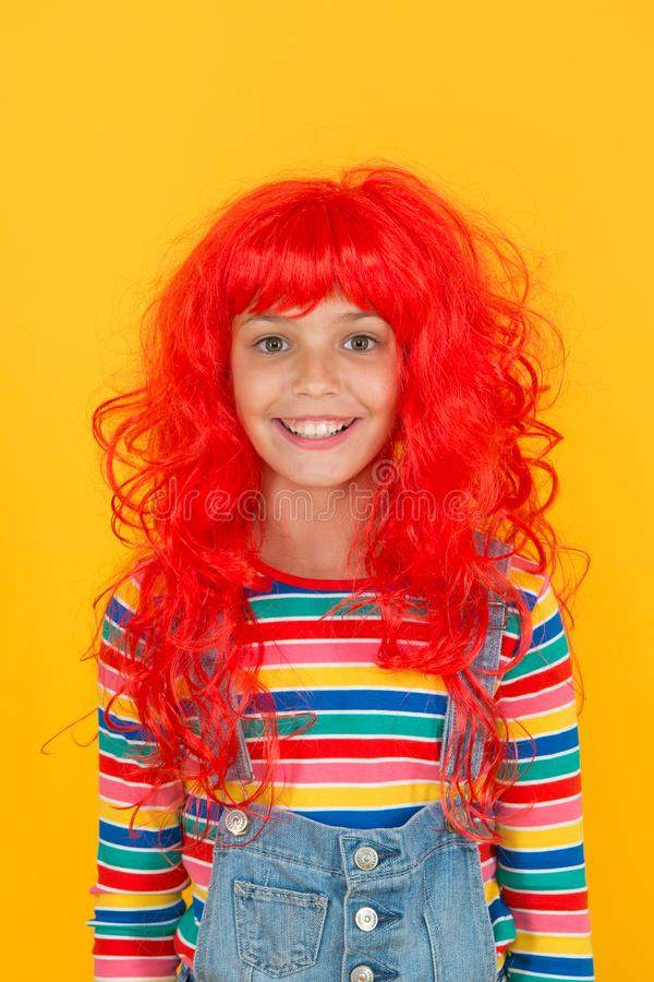 Ready for super party. Party girl yellow background. Happy child wear red colored party wig. Perfect look for cosplay or royalty free stock photos