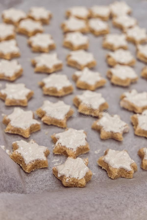 Ready to bake cinnamon star Christmas cookies with glazing on ba. King paper - uncooked - shallow depth of field stock photos