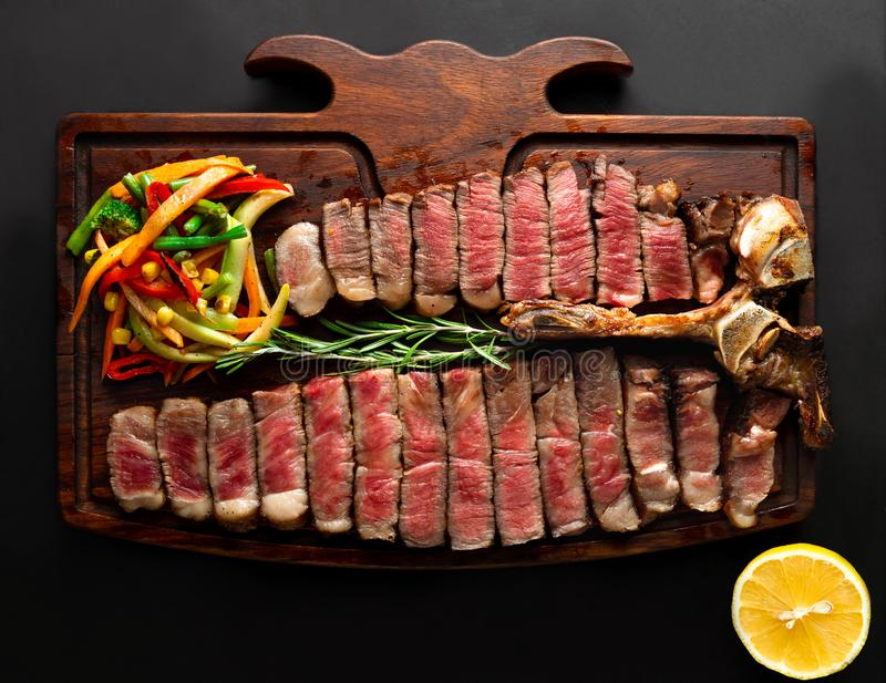 Ready to be served porterhouse steak with vegetables on wooden serving board royalty free stock photography