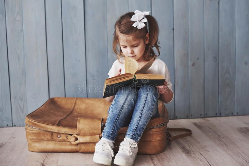 Ready to big travel. Happy little girl reading interesting book carrying a big briefcase. Freedom and imagination stock photo