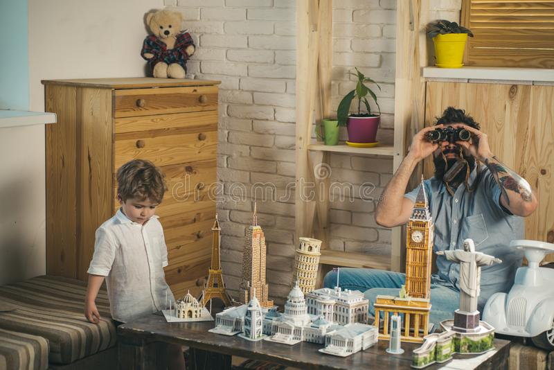 Ready to big travel. Little child and man with binocular and miniature architecture. Boy son and father with world. Ready to big travel. Little child and men royalty free stock images