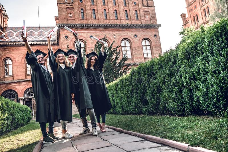 Ready to bright future! Four college graduates showing their diplomas and smiling while standing in university royalty free stock photography