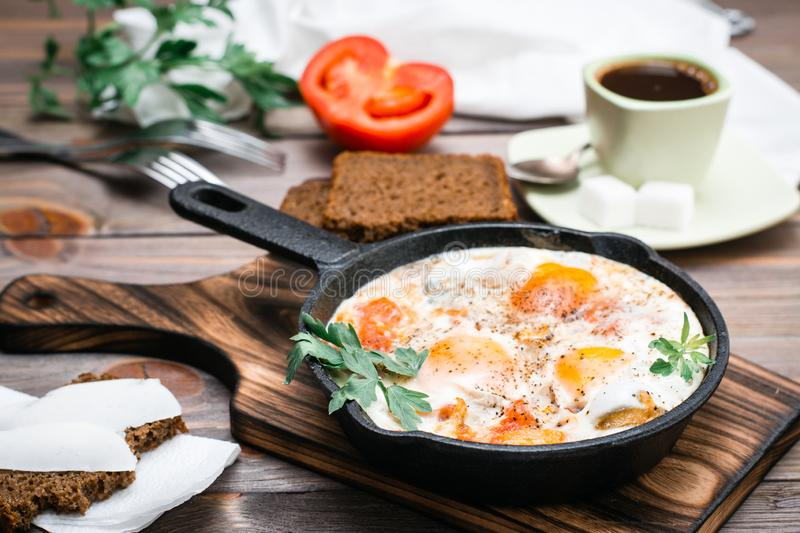 Ready-to-eat breakfast: shakshuka from fried eggs with tomatoes and parsley in a pan, bread with butter and coffeee. On a wooden table stock photo