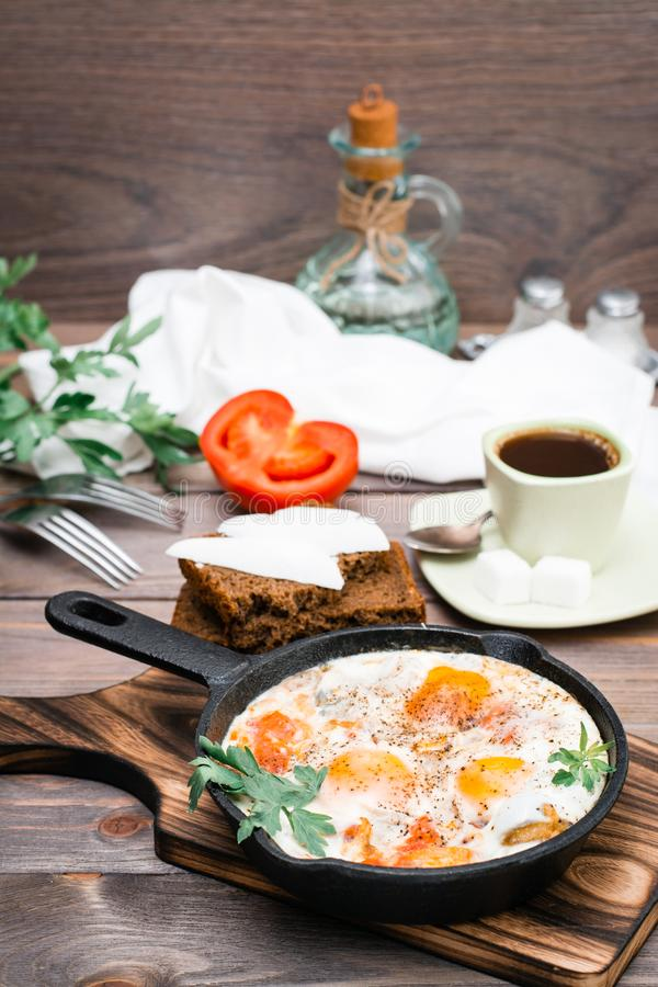 Ready-to-eat breakfast: shakshuka from fried eggs with tomatoes and parsley in a pan, bread with butter and coffeee. On a wooden table royalty free stock image