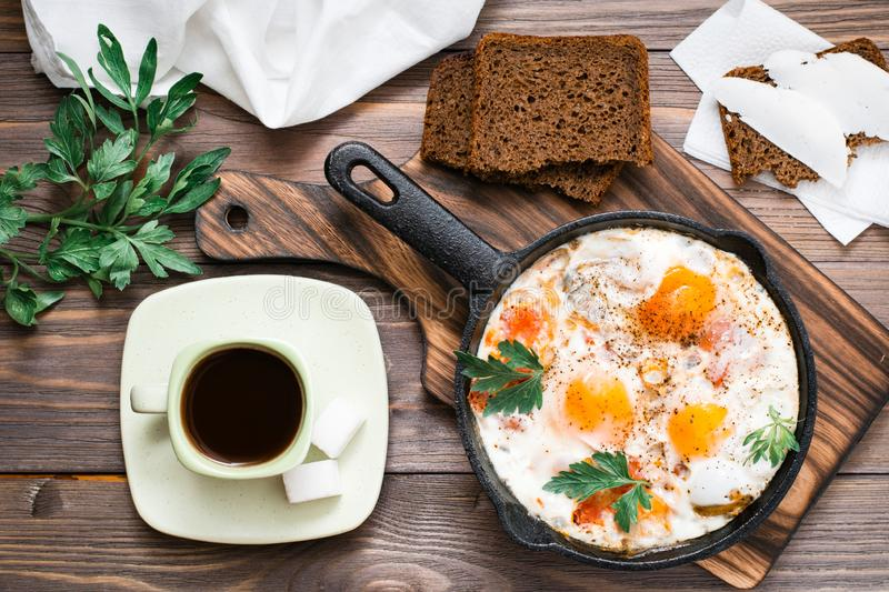 Ready-to-eat breakfast: shakshuka from fried eggs with tomatoes and parsley in a pan, bread with butter and coffeee. On a wooden table. Top view royalty free stock image