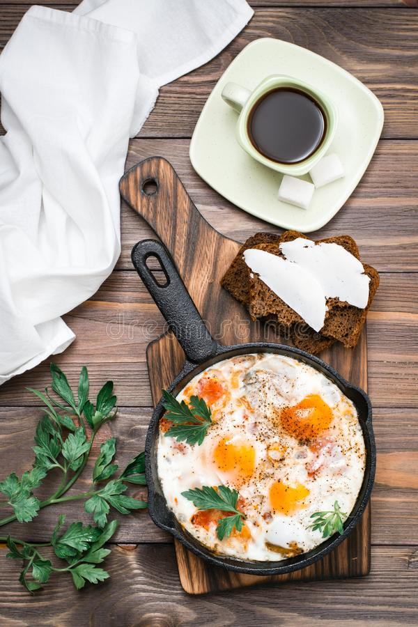 Ready-to-eat breakfast: shakshuka from fried eggs with tomatoes and parsley in a pan, bread with butter and coffeee. On a wooden table. Top view stock image