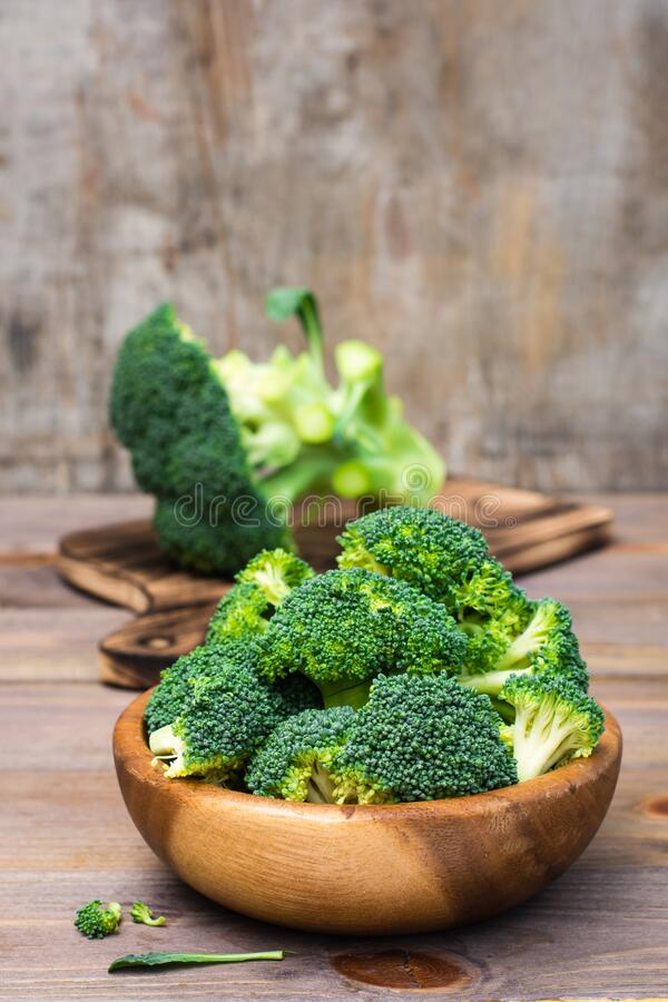 Ready to eat fresh raw broccoli is divided into inflorescences in a wooden plate on a wooden table. Healthy lifestyle, nutrition. And zero waste concept stock photo