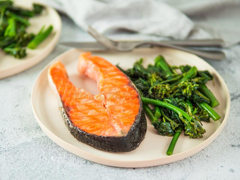 Ready-to-eat grilled salmon steak and greens stock image