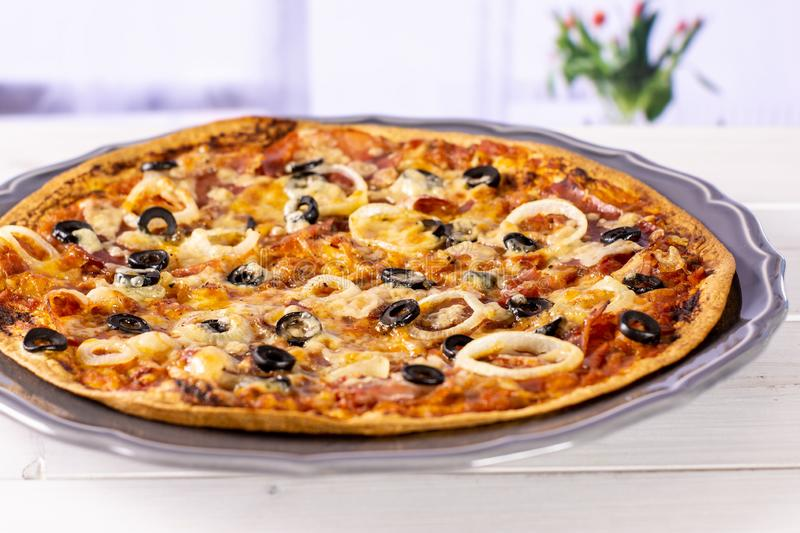 Recipe of pizza capriciosa with red tulips. Ready to eat. recipe step by step pizza capricciosa on grey ceramic plate in a white kitchen with flowers stock images