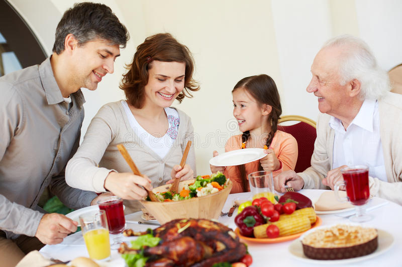 Ready to eat. Woman giving salad to her daughter royalty free stock images
