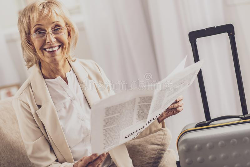 Delighted businesswoman waiting for her flight. Ready to go. Cheerful female person expressing positivity while holding newspaper, looking at camera stock image