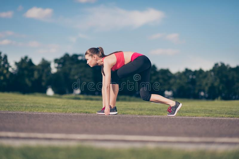 Ready to go! Female athlete on the starting line of a stadium tr. Ack, preparing for a run. Sunny spring day, young sport lady is in a fashionable outfit stock photography