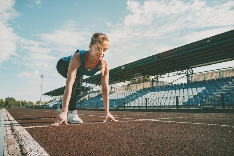 Ready to go. Young fitness blonde girl wearing blue top, black tights, sneakers and pony-tail on the starting line of royalty free stock image