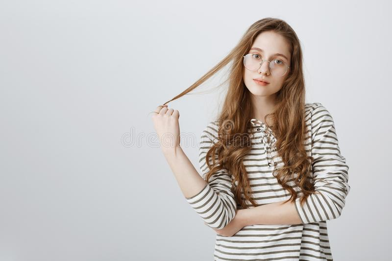 Ready to hear you out and help with suggestion. Carefree attractive teenager playing with hair and looking focused at. Camera, spacing out while hearing boring royalty free stock images