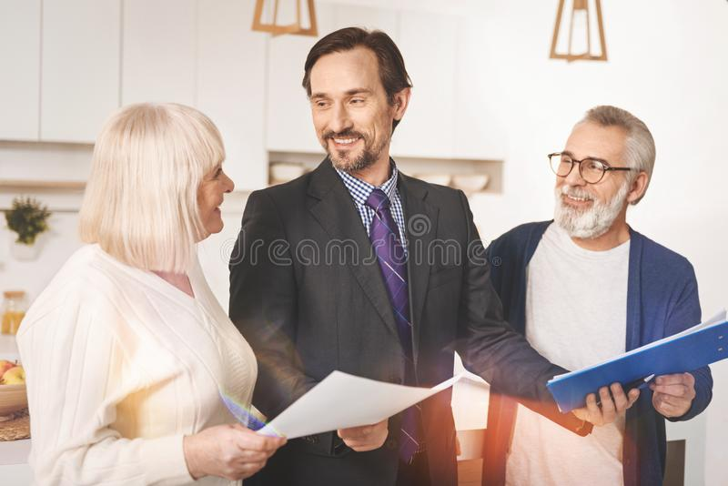 Cheerful insurance agent working with retired couple. Ready to help. Positive handsome insurance agent holding papers and working with retired couple at home royalty free stock image
