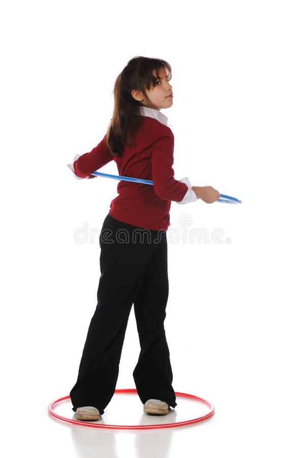 Ready to Hula Hoop. An older elementary girl twisting as she starts to spin a hoola hoop. Isolated on white royalty free stock image