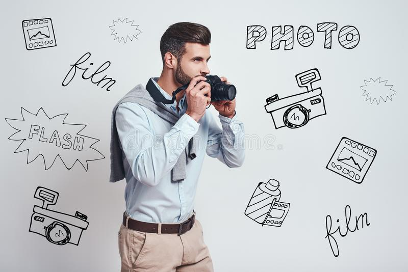 Ready to make a photo. Young attractive man is going to make a photoon digital camera while standing against grey royalty free stock images