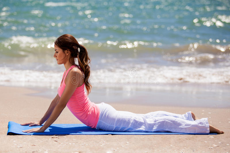 Ready to practice some yoga. Beautiful young brunette laying on a mat on the beach before doing some yoga stock photography