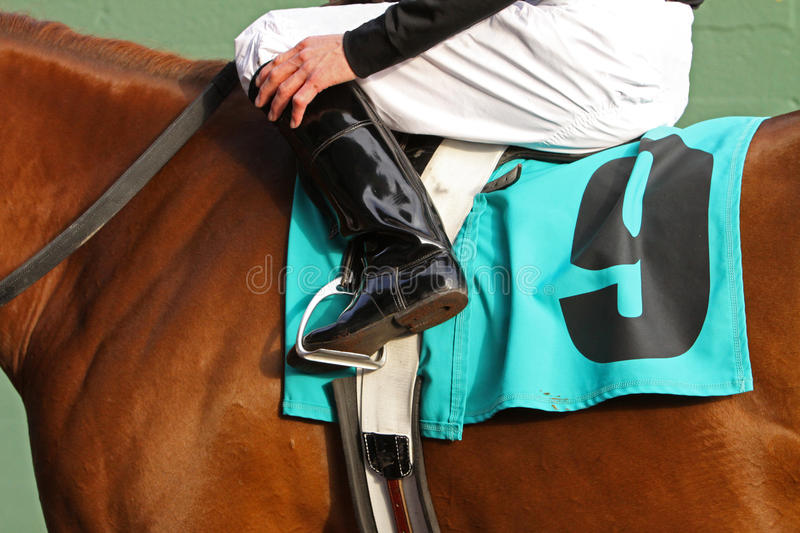 Ready to Race 2. Close up of jockey sitting in saddle of thoroughbred race horse. Focus on boot and stirrup stock images