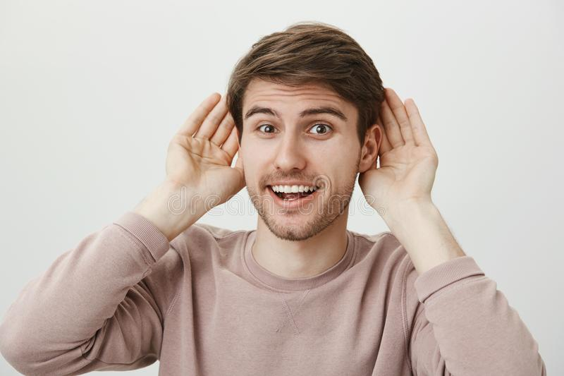 Ready to receive new information. Studio portrait of attractive positive guy holding palms near ears and smiling happily. Hearing rumor or eavesdropping royalty free stock photography