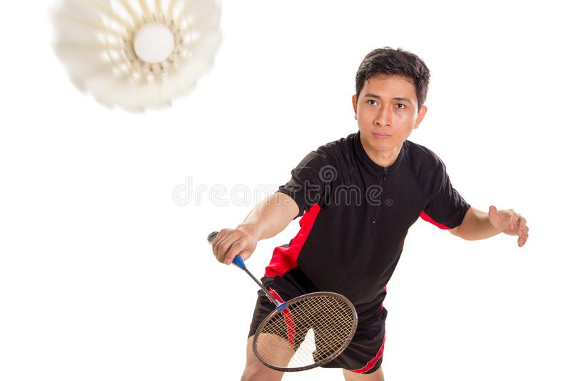Ready to return the shuttlecock. Badminton player ready to return the shuttlecock with backhand technique, isolated over white background royalty free stock image